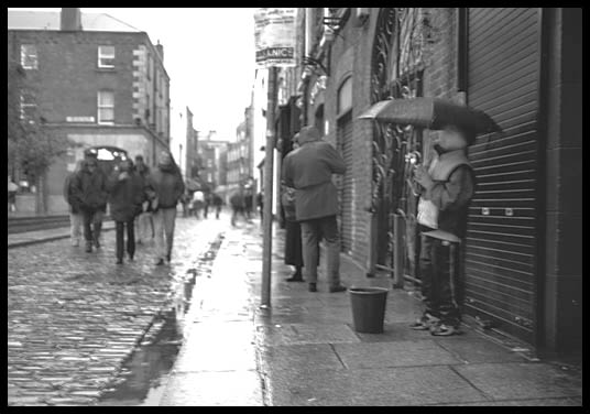Young boy busking in the Dublin rain